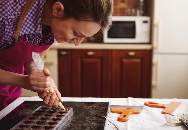 世界のチョコレートの日を祝うために家庭の台所で豪華な手作りチョコレートプラリネの準備を楽しんでいる笑顔のショコラティエ