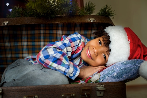 スーツケースの中の笑顔のクリスマスの子供。アフリカ系アメリカ人の子供の幸せなクリスマスの笑顔。家の暖かさ。そのような日は記憶にとどまります。