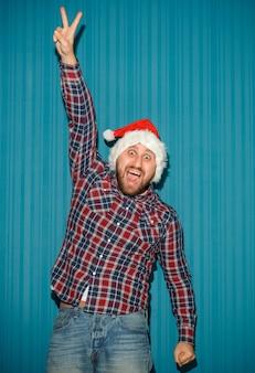 青いスタジオでサンタの帽子をかぶって笑顔のクリスマスの男