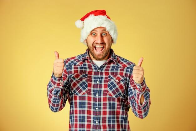 記号の付いたオレンジ色のスタジオでサンタ帽子をかぶっている笑顔のクリスマス男
