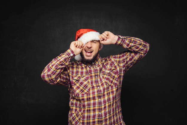 Smiling christmas man wearing a santa hat isolated on black