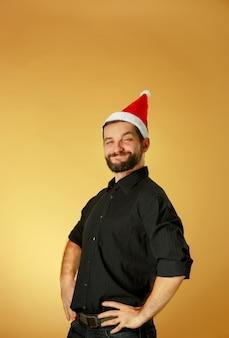 Sorridente uomo di natale che indossa un cappello da babbo natale sullo sfondo arancione dello studio