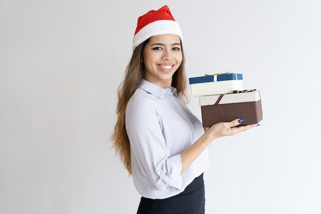 Smiling christmas office assistant carrying gifts