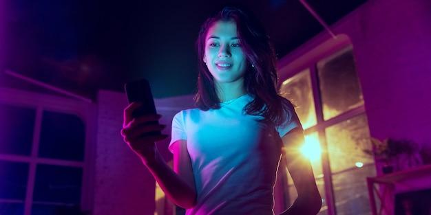 미소. 네온 조명이 켜진 실내에서 잘생긴 세련된 여성의 영화적 초상화. 보라색 - 파란색의 영화 효과처럼 톤. 실내에서 화려한 조명으로 스마트폰을 사용하는 백인 여성 모델. 전단.