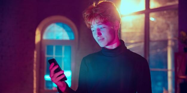 미소. 네온 조명이 켜진 실내에서 세련된 빨강머리 남자의 영화적 초상화. 보라색 - 파란색의 영화 효과처럼 톤. 실내에서 화려한 조명으로 스마트폰을 사용하는 백인 모델입니다. 전단.
