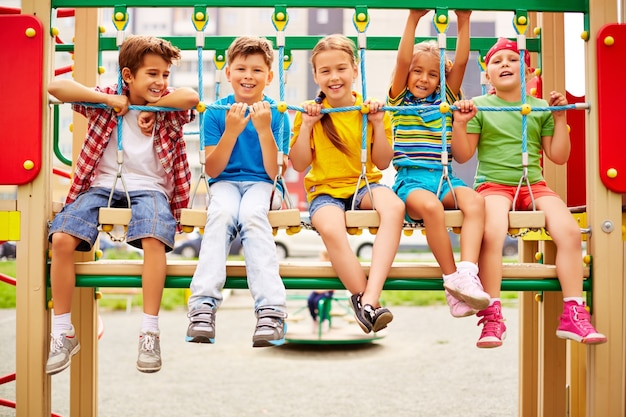 Smiling classmates sitting in a row on the playground