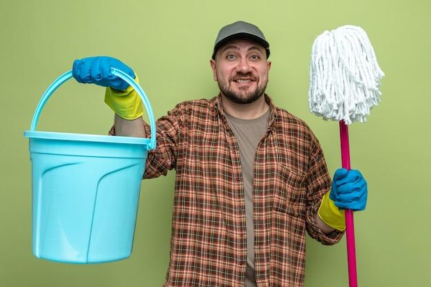 Sorridente uomo delle pulizie con guanti di gomma che tengono secchio e mocio