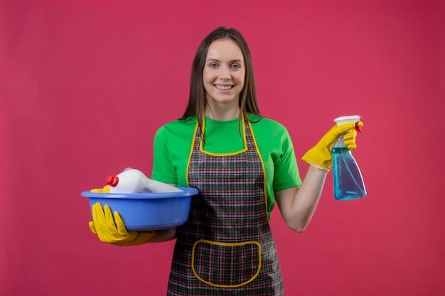 Sorridente pulizia ragazza giovane indossa uniforme in guanti che tengono strumenti di pulizia e spray per la pulizia isolato su sfondo rosa