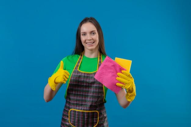 Sorridente ragazza giovane pulizia indossando uniformi in guanti che tengono gli strumenti di pulizia il suo pollice in alto su sfondo blu isolato