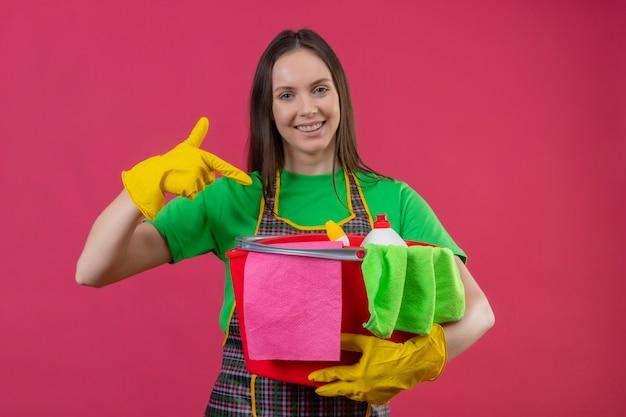 La ragazza sorridente di pulizia che indossa l'uniforme in guanti indica il dito agli strumenti di pulizia sulla sua mano su fondo rosa isolato