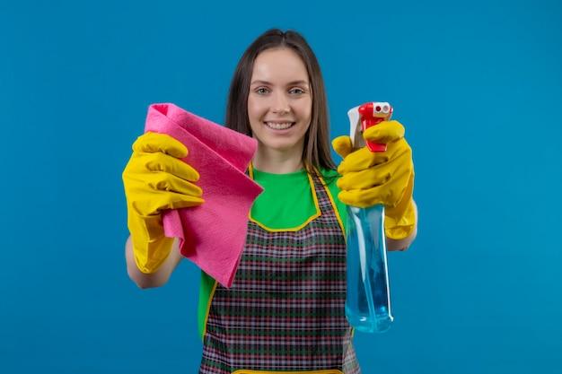 孤立した青い背景の上のカメラにクリーニングスプレーとぼろきれを差し出す手袋で制服を着て笑顔のクリーニングの若い女の子