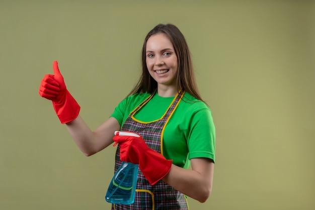 孤立した緑の背景に彼女の親指を上に掃除スプレーを保持している赤い手袋で制服を着て笑顔の掃除の若い女の子