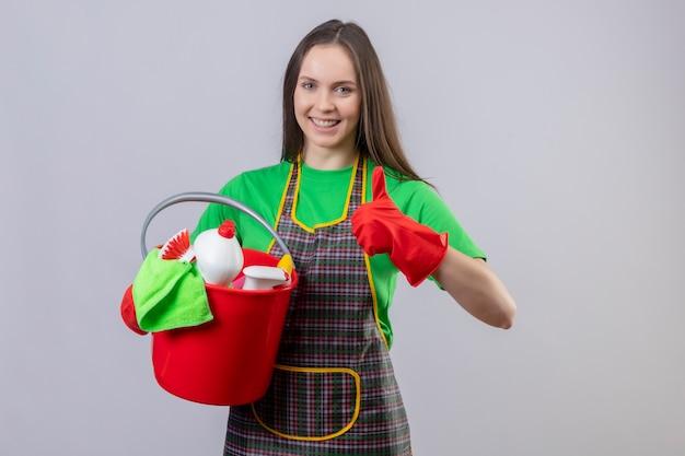 孤立した白い背景に彼女の親指をクリーニングツールを保持している赤い手袋で制服を着て笑顔のクリーニングの若い女の子
