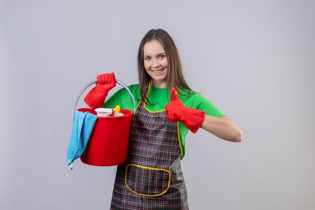 Sorridente ragazza giovane pulizia indossando l'uniforme in guanti rossi tenendo gli strumenti di pulizia il pollice in alto su sfondo bianco isolato