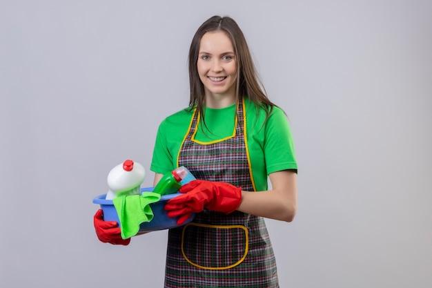 Sorridente pulizia ragazza giovane indossa uniforme in guanti rossi che tengono gli strumenti di pulizia su sfondo bianco isolato