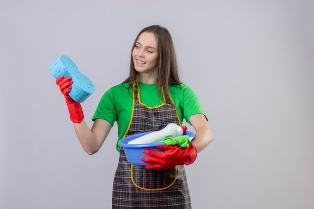 Sorridente ragazza giovane pulizia indossando uniformi in guanti rossi in possesso di strumenti per la pulizia guardando la spugna sulla sua mano su sfondo bianco isolato