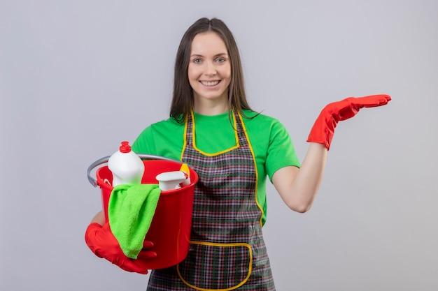 Sorridente ragazza giovane pulizia indossando uniformi in guanti rossi in possesso di strumenti di pulizia alzando la mano su sfondo bianco isolato