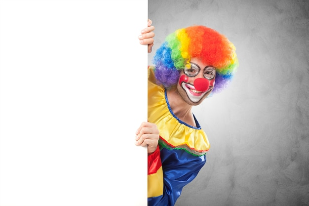 Smiling clown holding a blank panel
