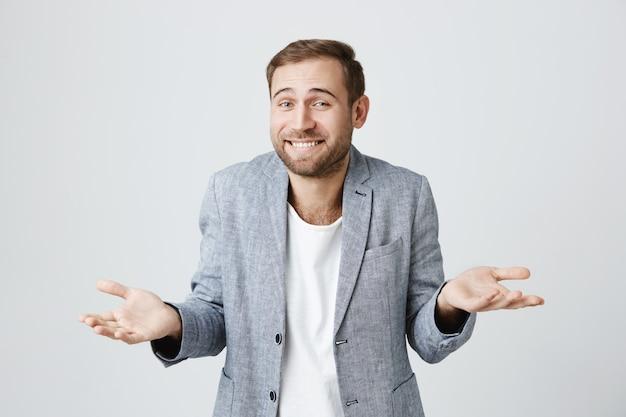 Улыбающийся невежественный парень пожимает плечами и разводит руками в стороны