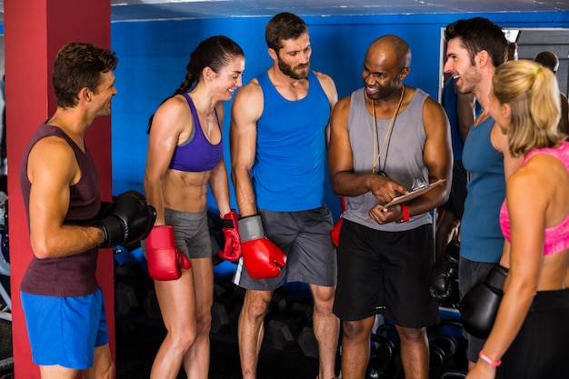 Smiling coach discussing with boxers