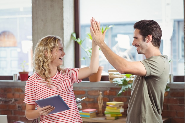 Smiling colleagues doing high five while working at creative office