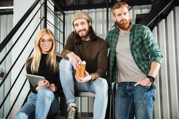 Smiling colleagues in office sitting on ladder