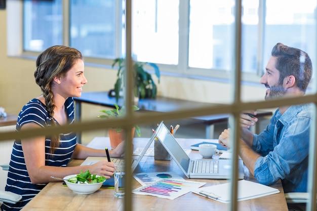 Улыбаясь коллег, работающих вместе на ноутбуке и обсуждения