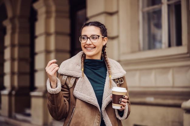 キャンパスでジャケットの立っているとコーヒーと使い捨てカップを保持している笑顔の大学生の女の子。彼女は次のクラスが始まるのを待っています。