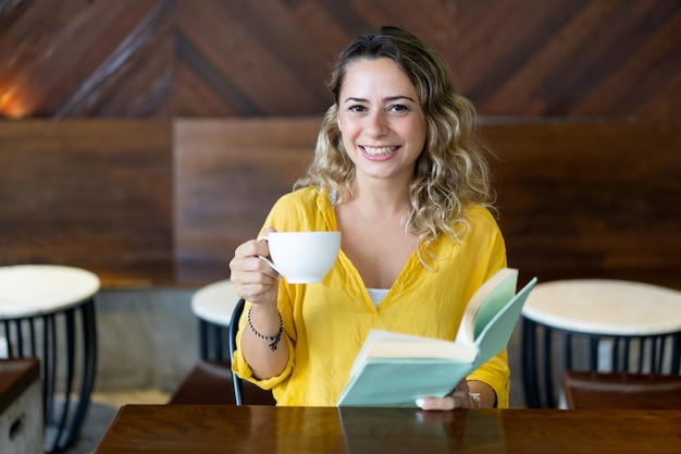 Smiling college student spending time in cafe
