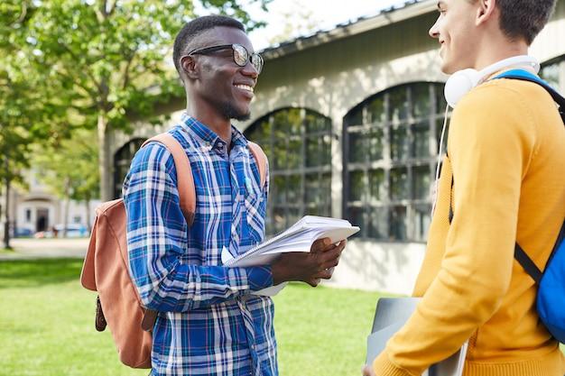 Улыбающиеся студенты колледжа в чате на открытом воздухе