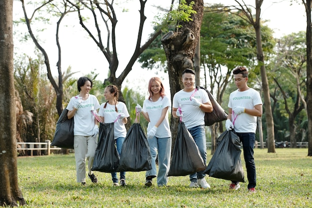 Smiling college students volunteering in city park or on campus and collecting garbage in big trash bags