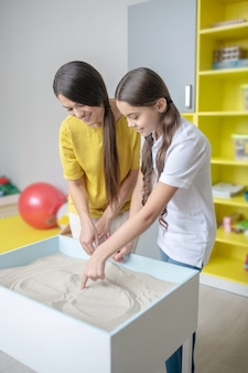 Smiling communicating young woman and school girl painting with sand during therapy session