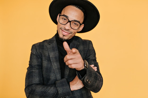 笑顔の自信を持ってアフリカ人の人差し指。黄色の壁に分離された茶色の肌を持つハンサムな男性モデルの肖像画。