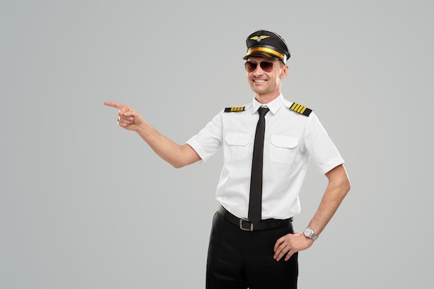 Smiling confident airline pilot pointing finger away
