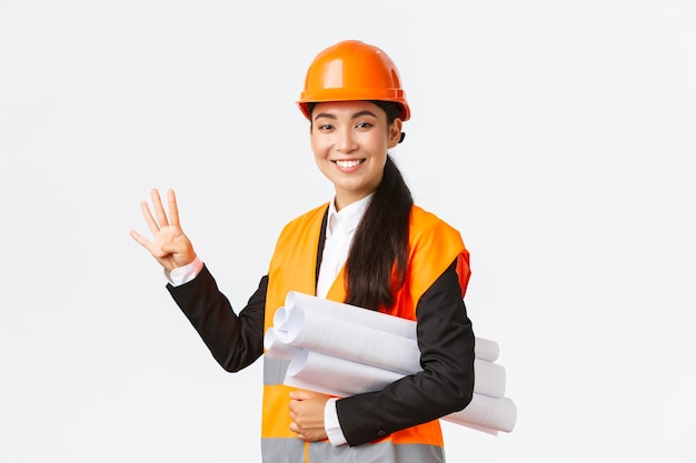 自信を持って笑顔のアジアの女性エンジニア、安全ヘルメットの建設マネージャー、青写真を運び、4本の指を見せ、建物が時間内に完成し、白い背景が明るいことを確認します