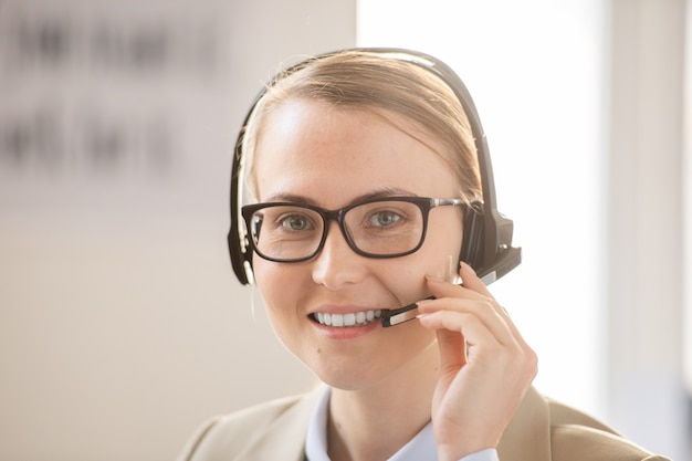 Smiling confident attractive call center agent in hands-free device and glasses looking