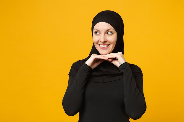 Smiling confident beautiful young arabian muslim woman in hijab black clothes posing isolated on yellow wall, portrait. people religious islam lifestyle concept.