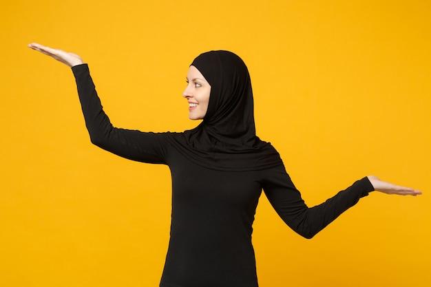 노란색 벽에 고립 된 포즈 hijab 검은 옷에 자신감이 아름 다운 젊은 아라비아 무슬림 여성 미소, 초상화. 사람들이 종교 이슬람 라이프 스타일 개념.