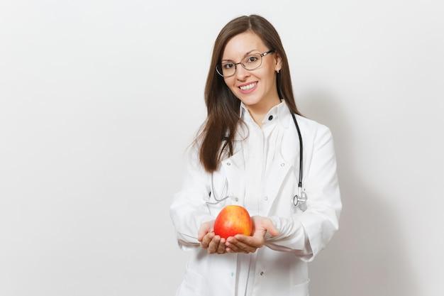 Усмехаясь уверенно красивая молодая женщина доктора со стетоскопом, стеклами изолированными на белой предпосылке. женщина-врач в медицинском халате, держа красное яблоко. медицинский персонал, здоровье, концепция медицины.