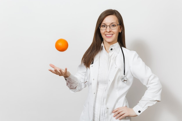 청진 기, 흰색 배경에 고립 된 안경 자신감이 아름 다운 젊은 의사 여자 웃 고. 오렌지를 토하고 의료 가운에 여성 의사입니다. 의료 인력, 건강, 의학 개념입니다.