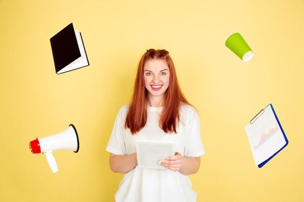 웃고, 자신감. 노란색 스튜디오에 백인 젊은 여자의 초상화