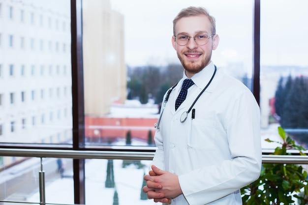 Улыбающийся уверенно врач на стойке регистрации, медицинский персонал, работающий на заднем плане