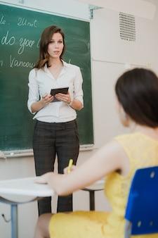 태블릿 pc와 자신감 여성 교사 미소는 칠판 앞에 서 그녀의 손에 개최