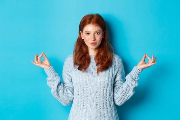 Улыбающаяся уверенная в себе девушка с рыжими волосами, оставаясь терпеливой, держась за руки в дзен, позе медитации и глядя в камеру, занимаясь йогой, спокойно стоя на синем фоне.