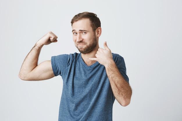 自信を持って笑顔の男性フィットネスインストラクター上腕二頭筋を曲げ、電話ジェスチャーを行う