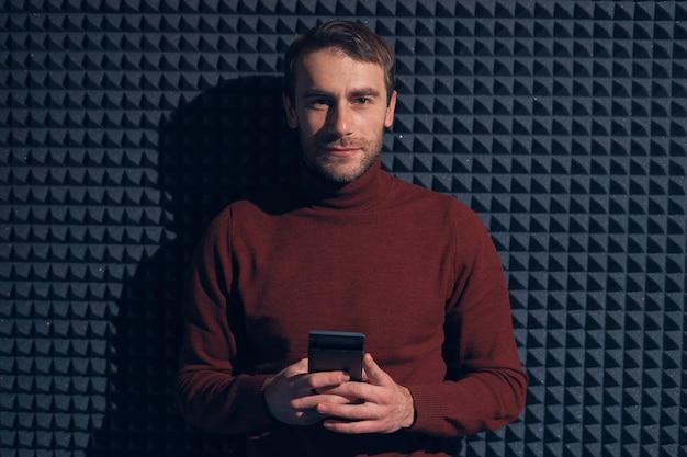Улыбающийся уверенный мужчина, держащий смартфон на сером фоне с геометрическими формами и легкой игрой.