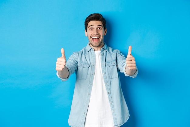 青い背景に立って、何か素晴らしい、承認製品のように、興奮した顔で親指を見せて笑顔の自信のある男