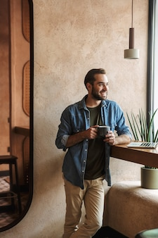 Smiling confident man wearing denim shirt drinking coffee with laptop while working in cafe indoors
