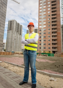Smiling confident worker in helmet and safety vest standing on building site