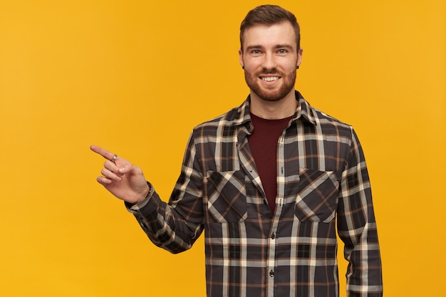 Smiling confident young bearded man in plaid shirt standing and pointing away at empty space by finger over yellow wall looking at front